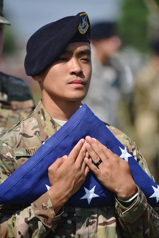 U.S. Air Force Senior Airman Yanny Nguyen, a defender assigned to the 509th Security Forces Squadron, holds the U.S. flag during a flag folding ceremony in remembrance of the six fallen Airmen of Charlie Fire Team at Whiteman Air Force Base, Missouri, June 10, 2018