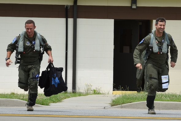 U.S. Air Force Lt. Col. Jeffrey Beckham, right, and Maj. Justin Dumais, pilots from the 169th Fighter Wing, scramble to their F-16 fighter jets for an Aerospace Control Alert training mission, June 5.The 169th FW, in close coordination with the Continental U.S. North American Aerospace Defense Command Region, the Eastern Air Defense Sector and the Federal Aviation Administration, hosted the Southeast Aerospace Control Alert Conference at McEntire Joint National Guard Base, S.C., June 5-7. The conference was a total team-training initiative to improve homeland-defense capabilities by developing techniques with joint forces during small-scale exercises. This conference consisted of South Carolina Air National Guard 169th FW F-16 fighter jets, U.S. Coast Guard Rotary Wing Air Intercept Squadron MH-65D Dolphin helicopters from USCG Air Station Atlantic City, and South Carolina Wing Civil Air Patrol aircraft and crews to hone their skills with tactical-level air-intercept procedures. (U.S. Air National Guard photo by Senior Master Sgt. Edward Snyder)