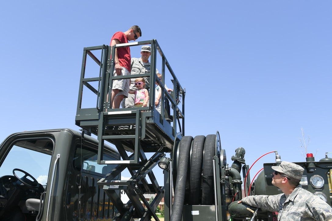 Haidyn and Nixon Sullivan with father Kasey receive a lift on a hydrant refueling truck from Tech. Sgt. T.W. Diamond and Airman 1st Class Wyatt Crothers, both with 75th Logistics Readiness Squadron, June 8, 2018, at Hill Air Force Base, Utah. Wheels of Wonder provides base families a fun, hands-on experience exploring various types of vehicles. (U.S. Air Force photo by Cynthia Griggs)