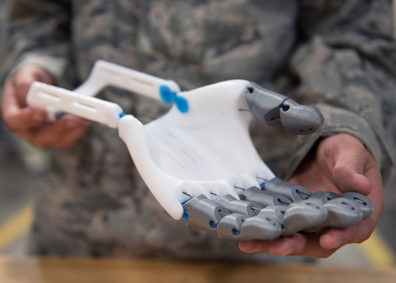 U.S. Air Force Senior Airman Timothy Bergin, 33rd Maintnenance Squadron aircraft metals technology journeyman, holds his prototype prosthetic June 13, 2018, at Eglin Air Force Base, Fla. Bergin found a model of a prosthetic online and began customizing it to improve functionality, lifespan and appearance. In addition to improvements, he says he can reproduce the hand for less than $20. (U.S. Air Force photo by Staff Sgt. Peter Thompson)