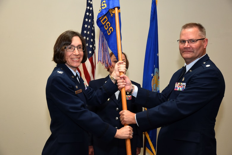 U.S. Air Force Col. Janet Urbanski, 17th Medical Group commander, passes the 17th Medical Support Squadron guideon to Lt. Col. Warren Conrow, 17th MDSS incoming commander, at the 17th MDSS Change of Command at the Event Center on Goodfellow Air Force Base, Texas, June 15, 2018. The change of command ceremony is a time honored military tradition that signifies the orderly transfer of authority. (U.S. Air Force photo by Airman 1st Class Seraiah Hines/Released)