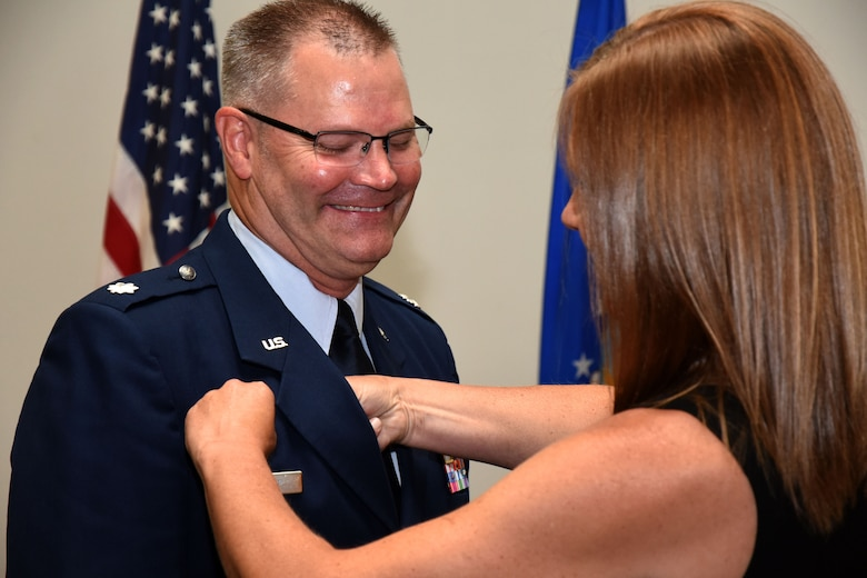 U.S. Air Force Lt. Col. Warren Conrow, 17th Medical Support Squadron incoming commander, receives his commander's pin from his spouse during the 17th MDSS Change of Command at the Event Center on Goodfellow Air Force Base, Texas, June 15, 2018. The pin indicates that an individual holds the position of commander of a squadron, group, wing or major command. (U.S. Air Force photo by Airman 1st Class Seraiah Hines/Released)