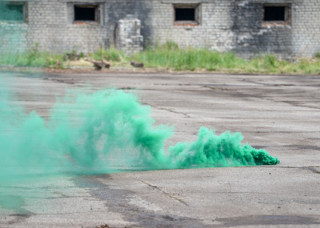 Green smoke marks the landing zone for a Latvian MI-17 Helicopter to land for a simulated medical evacuation during an exercise in Skrunda, Latvia on June 13, 2018. The battle was part of Saber Strike 18 and pieced together communication, tactics, and other facets of military operation into one scenario. (U.S. Air Force photo by Staff Sgt. Jimmie D. Pike)