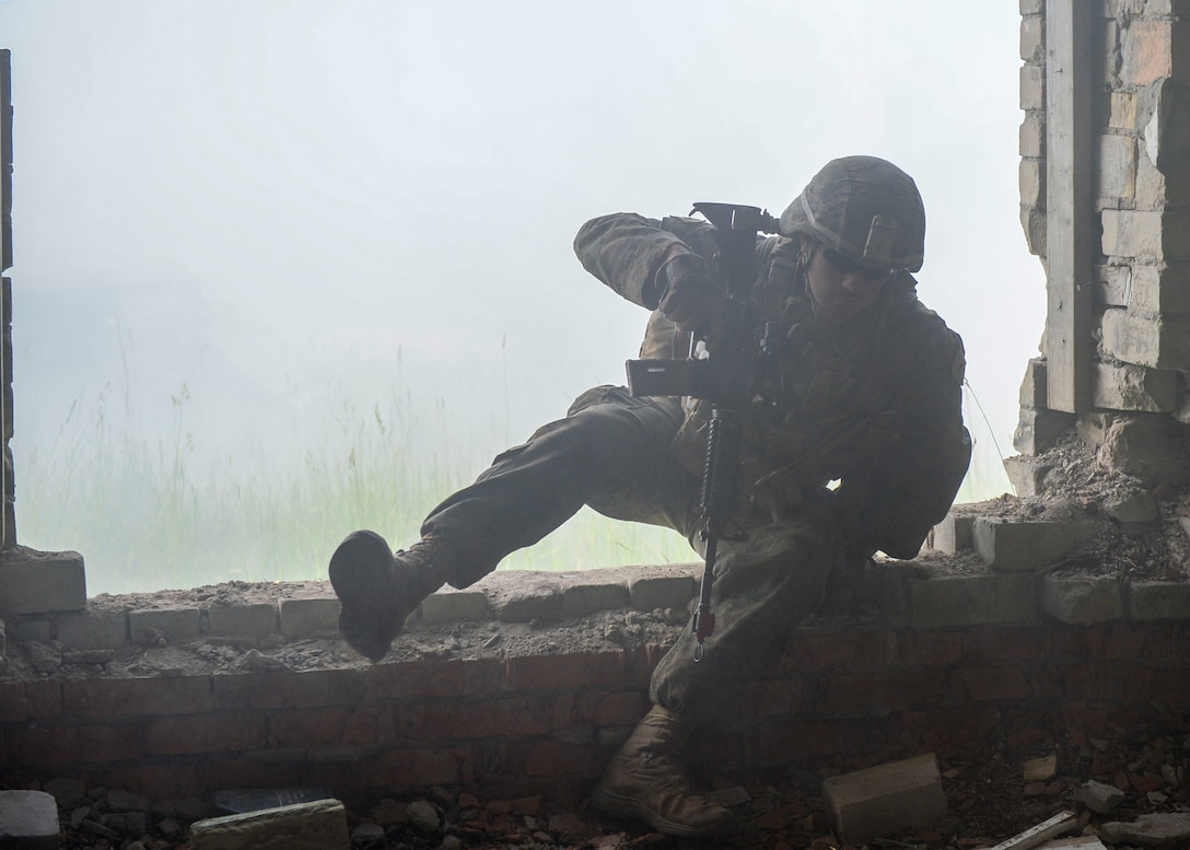 A U.S. Marine breaches a building during a large scale battle scenario during Saber Strike 18 in Skrunda, Latvia on June 13, 2018. U.S Marines teamed with United Kingdom Royal Marines, Michigan Army National Guard, and Norwegian Forces as the attacking force whose objective was to remove opposing forces. Saber Strike aims to improve strategic partnerships, ability to operate in the dynamic security environment, and to maintain readiness of forces. (U.S. Air Force photo by Staff Sgt. Jimmie D. Pike)