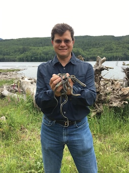 Seattle District fishery biologist Rafael Lopez-Gonzalez holds garter snakes above Howard Hanson Dam. Rafael is working with a team of herpetologist from U.S. Army Engineer Research and Development Center (ERDC) conducting field studies to survey for reptiles and amphibians at Mud Mountain Dam and Howard Hanson Dam.