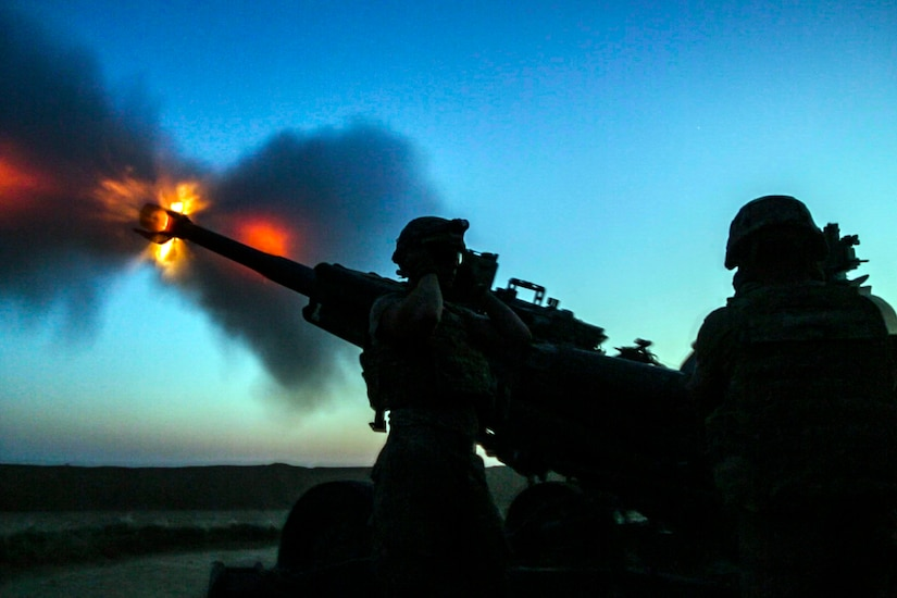 Soldiers fire artillery.