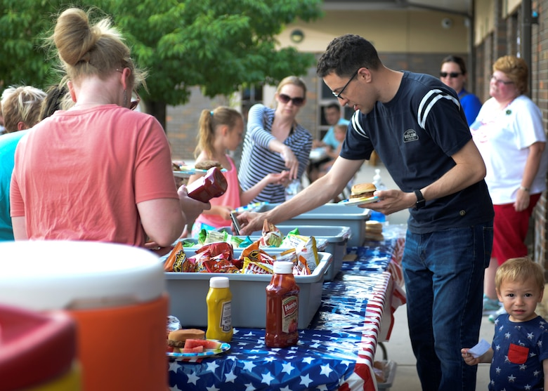 Families line up to get food at the Ellsworth Air Force Base Child Development Center's Eighth Annual Flag Day Picnic.  Ellsworth Child Development Center celebrated the national observance during their Eighth Annual Flag Day Picnic. (U.S. Air Force photo by Senior Airman Michella Stowers)