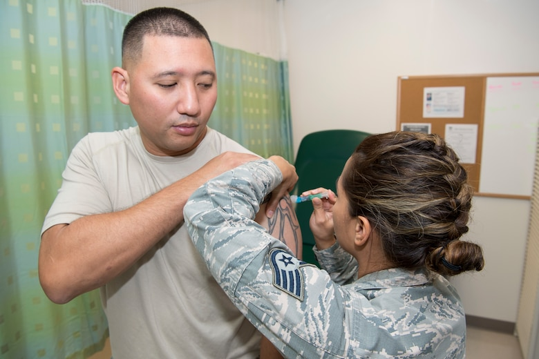 U.S. Air Force Staff Sgt. Ealani Flores, Air Force Reserve's 624th Aerospace Medicine Flight immunizations backup technician, administers a vaccination to 1st Lt. Tommy Rivera, Air National Guard's 254th Air Base Group cyberspace officer, as part of individual medical readiness requirements during a unit training assembly at Andersen Air Force Base, Guam, June 3, 2018.