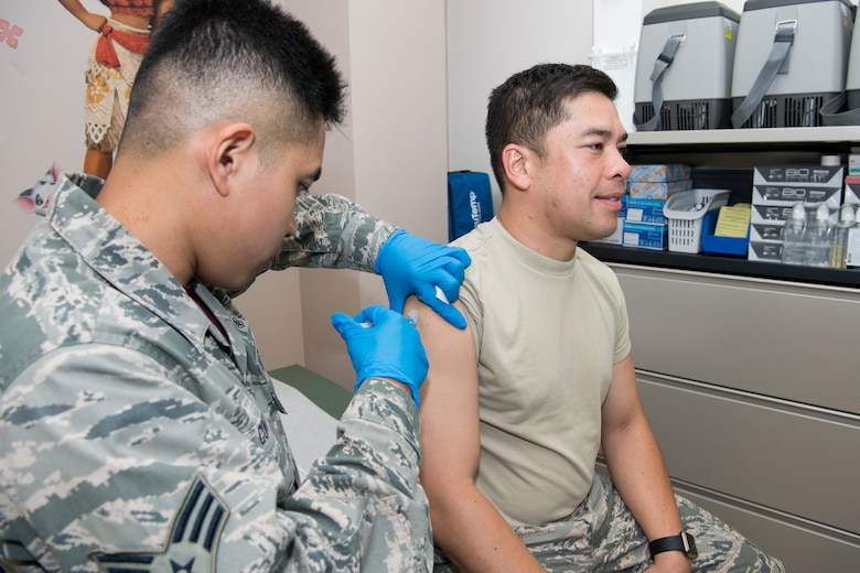 U.S. Air Force Senior Airman John Cortez, Air Force Reserve's 624th Aerospace Medicine Flight immunizations backup technician, administers a vaccination to Airman 1st Class Ryan Martinez, Air National Guard's 254th Air Base Group client systems specialist, as part of individual medical readiness requirements during a unit training assembly at Andersen Air Force Base, Guam, June 3, 2018.