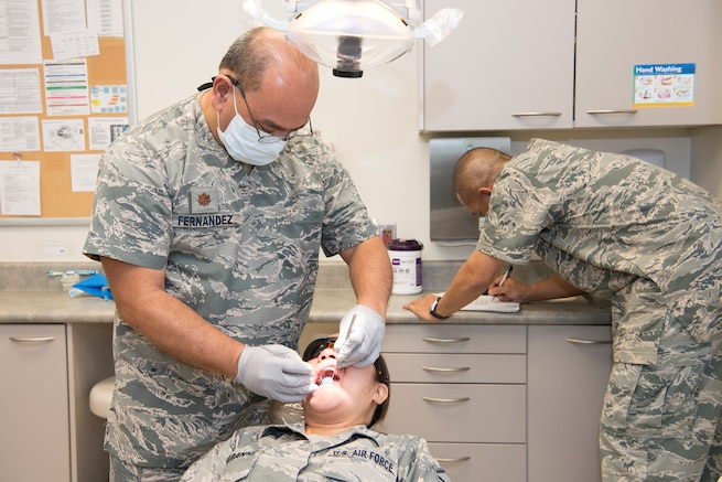 U.S. Air Force Maj. Michael Fernandez, Air Force Reserve's 624th Aerospace Medicine Flight chief dentist, conducts a dental exam for Master Sgt. Jean Chabanne, Air National Guard's 254th Air Base Group personalist, while Tech. Sgt. Vincent Nelson, 624th AMDF dental services non-commissioned officer in charge, scribes dental notes as part of individual medical readiness requirements during a unit training assembly at Andersen Air Force Base, Guam, June 3, 2018.