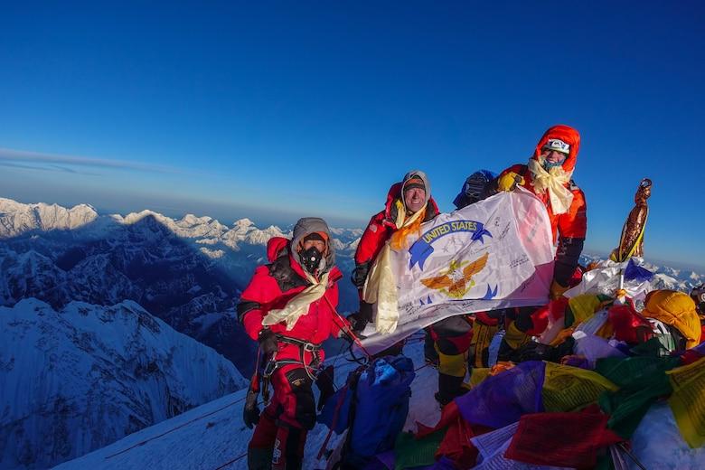 Matt Moniz, Mike Moniz, and guide pose for a photo on the summit of Mount Everest with a U.S. 7th Fleet flag.  Photo courtesy of the Moniz family.