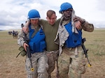 Alaska Army National Guard Spc. Dana Haddox and Spc. Jahmoi Hodge, both members of the platoon representing the 297th Regional Support Group, evacuate simulated casualty U.S. Navy Hospital Corpsman 3rd Class John Bustamonte, III Marine Expeditionary Force, June 17, 2018, during Tactical Combat Casualty Care training at Five Hills Training Area, Mongolia, as part of Khaan Quest 2018.