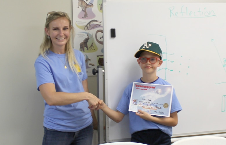 Olga Oakley, Air Force Science, Technology, Engineer and Development director, shakes the hand of the 2018 Reach for the Stars winner Evan Cain, whose rocket's average distance from the target was 33 feet 4 inches. (Courtesy photo)