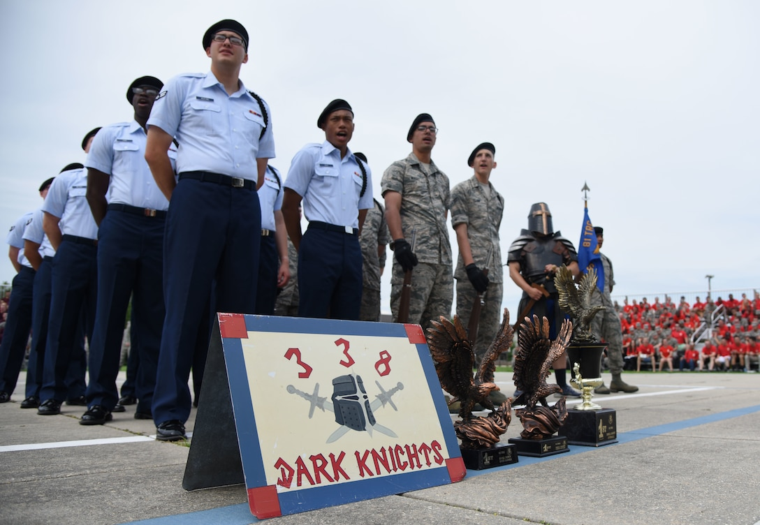 """Members of the 338th Training Squadron drill team stand in formation behind their winning trophies during the 81st Training Group drill down on the Levitow Training Support Facility drill pad at Keesler Air Force Base, Mississippi, June 15, 2018. Airmen from the 81st TRG competed in a quarterly open ranks inspection, regulation drill routine and freestyle drill routine. The 338th TRS """"Dark Knights"""" took first place overall this quarter. (U.S. Air Force photo by Kemberly Groue)"""