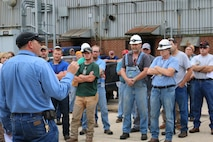 Ironworker Kevin Glaser, left, addresses fellow Manufacturing Group employees during a May 29 memorial held in honor of John Hill and Alvin Overman. Hill and Overman died on Dec. 10, 1971, after entering a confined space filled with argon gas. (U.S. Air Force photo/Bradley Hicks) (This image was manipulated by obscuring badges for security purposes)