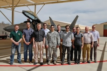 Arnold Engineering Development Complex Junior Force Council members pause for a photo in front of an F-22 Raptor during a tour of the 411th Combined Test Force at Edwards Air Force Base. Pictured from left are Nicholas Perry, Christopher Hartley, Brandon Hoffman, Dan Ogg, Capt. Michael Davault, Stephen Maccarino, Christopher Northrup, Michael Glennon, Becky Morris, Tyler McCamey and Elijah Minter. (U.S. Air Force photo/Christopher Higgins)