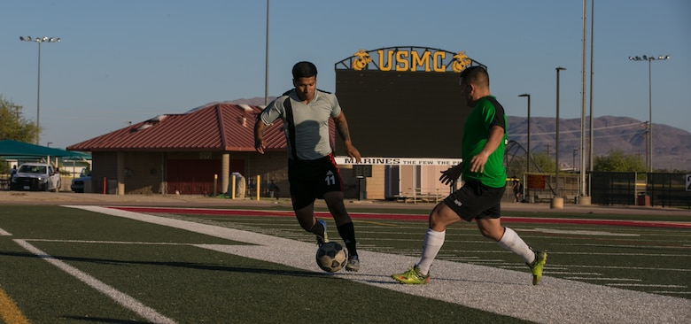 A member of the Marine Corps Communication-Electronics School's intramural soccer team takes the ball up the field during the installation's intramural soccer finals at Felix Field aboard the Marine Corps Air Ground Combat Center, Twentynine Palms, Calif., June 7, 2018. The MCCES team won 3-0, defeating the Headquarters' Battalion team. (U.S. Marine Corps photo by Lance Cpl. Dave Flores)