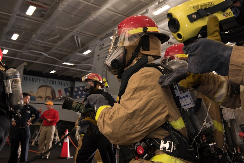 Navy Petty Officer 3rd Class Tilden Sansom uses a thermal imager during a firefighting drill in the hangar bay aboard the aircraft carrier USS Harry S. Truman in the Mediterranean Sea.