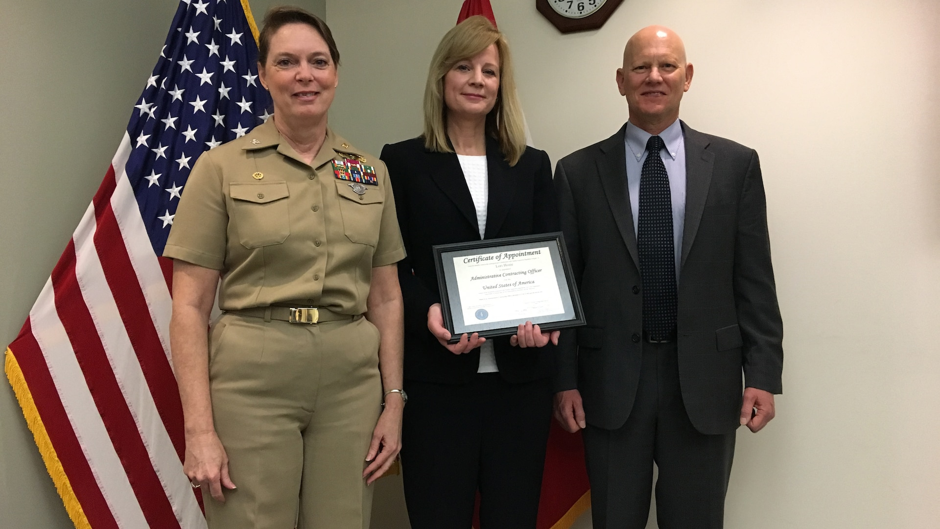 Commander of Defense Contract Management Agency International, Navy Capt. Sonya Ebright (left) and Robert Billington (right), DCMA Americas Director present Lori Hosie with her administrative contracting officer's warrant in Ottawa, Ontario, Canada March 20. Hosie is currently the only DCMA local national employee who holds an active warrant. (DCMA photo by Kelli Zagata)