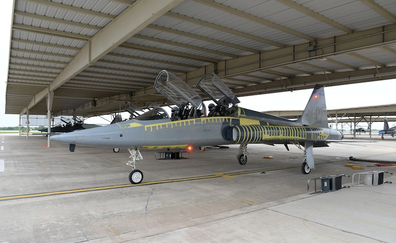 T-38C Talon Instructor Pilot (front), Lt. Col Edward Stapanon III, and Combat Systems Officer (rear), Maj. Brion Nielsen, taxi out from under the protective sunshades for a training mission April 18, 2018, at Joint Base San Antonio-Randolph, Texas. The aircraft recently completed the Pacer Classic III modification package and still shows its distinctive tiger stripes. (U.S. Air Force photo by Alex R. Lloyd)