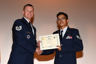 U.S. Air Force Tech. Sgt. Kyle Dobler, 312th Training Squadron fire inspector, hands Staff Sgt. Yamato Hart, 17th Civil Engineer Squadron Emergency Management journeyman, the Air Force Association Pitsenbarger Award during a Community College of the Air Force graduate ceremony at the base theater on Goodfellow Air Force Base, Texas, June 15, 2018. The award recognizes the students' activities that indicate excellent leadership, citizenship, teamwork, community service, personal development and dedication. (U.S. Air Force photo by Staff Sgt. Joshua Edwards/Released)