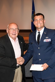 Retired U.S. Air Force Col. Charles Powell, former 17th Training Wing commander, hands Senior Airman Jacob Letson, 17th Civil Engineer Squadron engineering technician, the Powell Warrior Award during a Community College of the Air Force graduate ceremony at the base theater on Goodfellow Air Force Base, Texas, June 15, 2018. The award is given to CCAF graduates who have displayed the highest degree of professional military excellence. (U.S. Air Force photo by Staff Sgt. Joshua Edwards/Released)