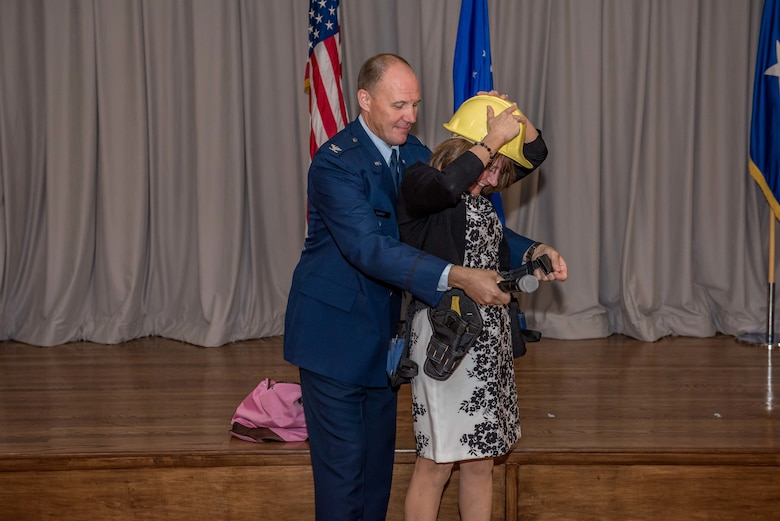 Col. Jason Schott gave his wife, Emily Schott, a hard hat and tool belt as a gift to help construct the house they plan to build in Colorado during his retirement. (Air Force Photo by Matt Williams)