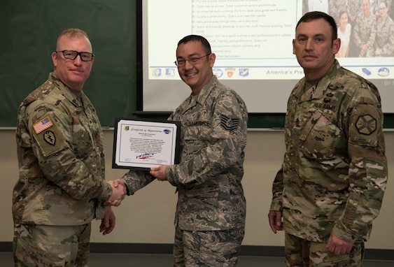 U.S. Army Col. Adam Lange, 673d Air Base Wing and Joint Base Elmendorf-Richardson vice-commander, and U.S. Army Sgt. Maj. Jerry Byrd, Garrison Sgt. Maj. for 673d Air Base Wing, present a certificate of recognition to a member of the JBER Hospital Laboratory, at JBER, Alaska, June 15, 2018. The certificate recognizes the team for exceptional customer service.