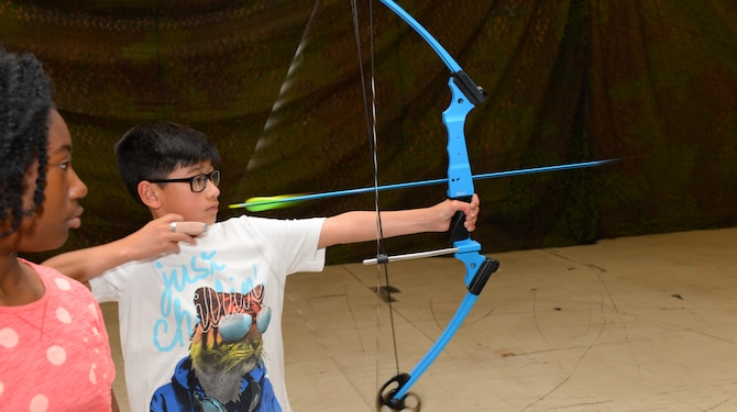 A child shoots an arrow during an archery training class put on by the Youth Center at Ellsworth Air Force Base, S.D., June 13, 2018. The Youth Center has five specialty courses planned for the summer months, including archery and music courses. (U.S. Air Force photo by Airman 1st Class Nicolas Z. Erwin)
