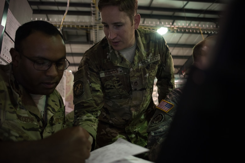 Master Sgt. Christopher Vaughn, 146th Air Support Operations Squadron (146th ASOS) tactical air control party (TACP) non-commissioned officer in charge, looks at notes with Staff Sgt. Samuel Salcedo, 146th ASOS TACP specialist, after receiving information during a combat scenario during Warfighter 18-5 (WFX-18-5) June 10, 2018, at Camp Atterbury Joint Maneuver Training Center near Edinburgh, Indiana. WFX-18-5 was conducted to help components under the 34th Infantry Division become accustomed to using Army battle drills in a computer-simulated combat environment. (U.S. Air National Guard photo by Staff Sgt. Brigette Waltermire)