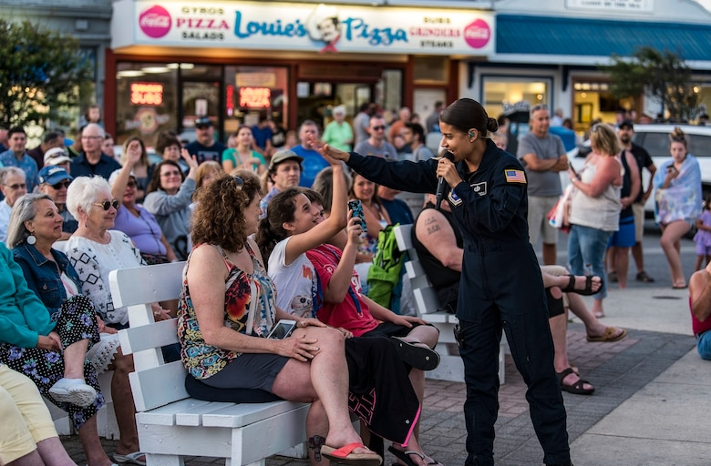 Tech. Sgt. Nalani Quintello, Max Impact vocalist, gives a high five to Gwennyth Farmer of Millsboro, Del., during the band's performance June 16, 2018, on the bandstand at Rehoboth Beach, Del. Max Impact performed 20 songs for hundreds of beachgoers during the free, public concert. Max Impact, the premier rock band of the U.S. Air Force, is stationed at Joint Base Anacostia-Bolling in Washington, D.C. (U.S. Air Force photo by Roland Balik)