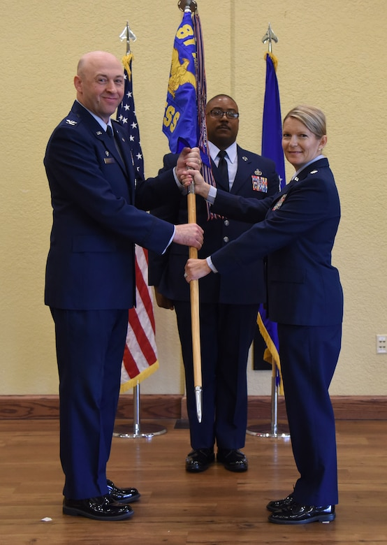 U.S. Air Force Col. Danny Davis, 81st Mission Support Group commander, takes the 81st Force Support Squadron guidon from Lt. Col. Teresa Ammons, outgoing 81st FSS commander, during the 81st FSS change of command ceremony in the Bay Breeze Event Center at Keesler Air Force Base, Mississippi, June 14, 2018. The passing of the guidon is a ceremonial symbol of exchanging command from one commander to another. (U.S. Air Force photo by Kemberly Groue)