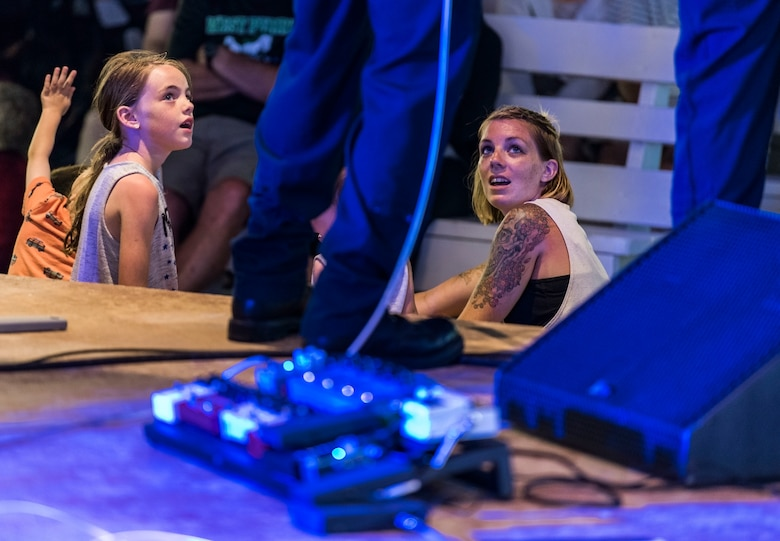 Two members of the audience listen to the band, Max Impact, as they perform June 16, 2018, on the bandstand at Rehoboth Beach, Del. Max Impact performed for more than an hour during the free, public Rehoboth Beach Bandstand Summer Concert Series. Max Impact, the premier rock band of the U.S. Air Force, is stationed at Joint Base Anacostia-Bolling in Washington, D.C. (U.S. Air Force photo by Roland Balik)
