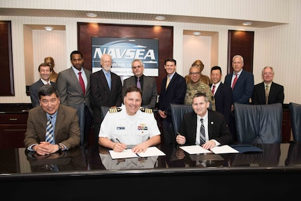 Naval Surface Warfare Center, Carderock Division Commanding Officer Capt. Mark Vandroff (center) and Technical Director (acting) Dr. Paul Shang (left) sign an Education Partnership Agreement with Dr. J. Scott Cameron (right) president of the National Intelligence University, in West Bethesda, Md., June 11, 2018. (Seated from left) Shang, Vandroff and Cameron. (Standing from left) Carderock Marine and Aviation Division Head Steve Ebner (Code 88), Carderock Patent Attorney Dave Ghatt, Carderock Director of Strategic Relations Dr. John Barkyoumb, NIU Professor Dr. Peter Leitner, NIU Dean of the School of Science and Technology Intelligence Dr. Brian Holmes, NIU faculty member MSG Angel Morales, Carderock Electrical Engineer Dr. Peter Cho (Code 88), Department Head Naval Architecture and Engineering Mike Brown and Carderock Director of Technology Transfer Dr. Joseph Teter (Code 00T). (U.S. Navy photo by Nicholas Brezzell/Released)