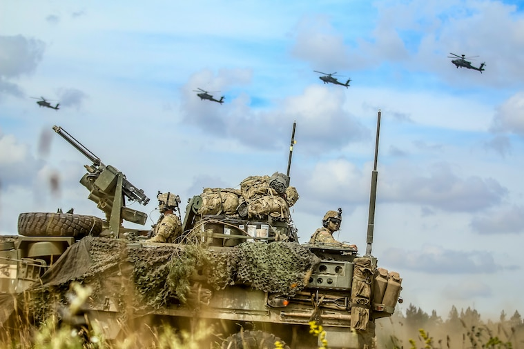 Helicopters fly over an armored vehicle.
