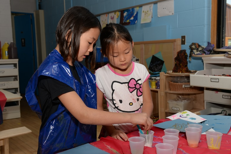 Two children paint pictures at the Youth Center on Ellsworth Air Force Base, S.D., June 13, 2018. The open recreation program during the summer consists of weekly field trips off base, family bonding events and weeklong specialty camps specializing in theater or music, where students can practice their talents in a professional recording studio. (U.S. Air Force photo by Airman 1st Class Nicolas Z. Erwin)
