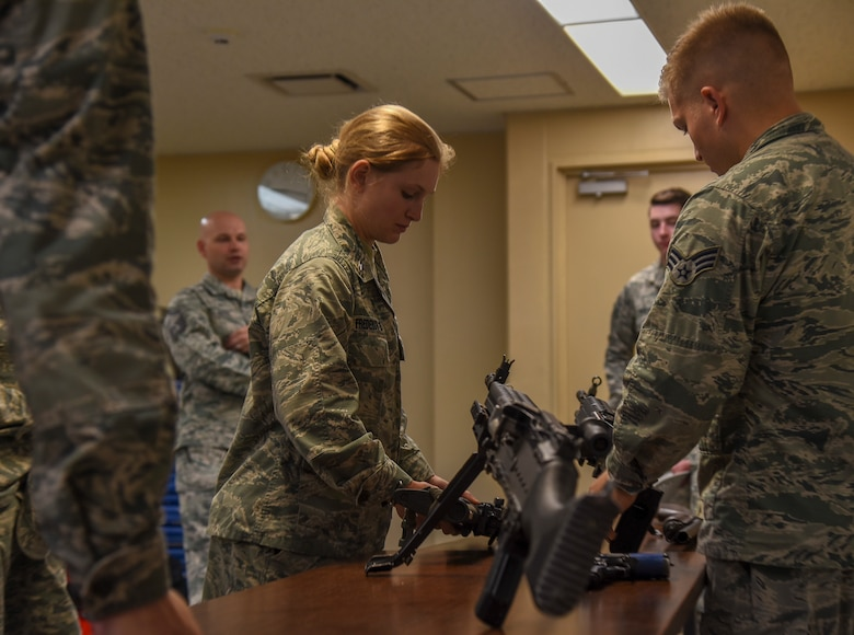 Cadet 2nd Class Jessica Frederick, a United States Air Force Academy cadet, examines a weapon on display during a security forces tour at Misawa Air Base, Japan, June 18, 2018. This demonstration was one of many the USAFA cadets had the opportunity to take part in during Operation Air Force, a two-week immersion into active duty Air Force life. (U.S. Air Force photo by Airman 1st Class Collette Brooks)