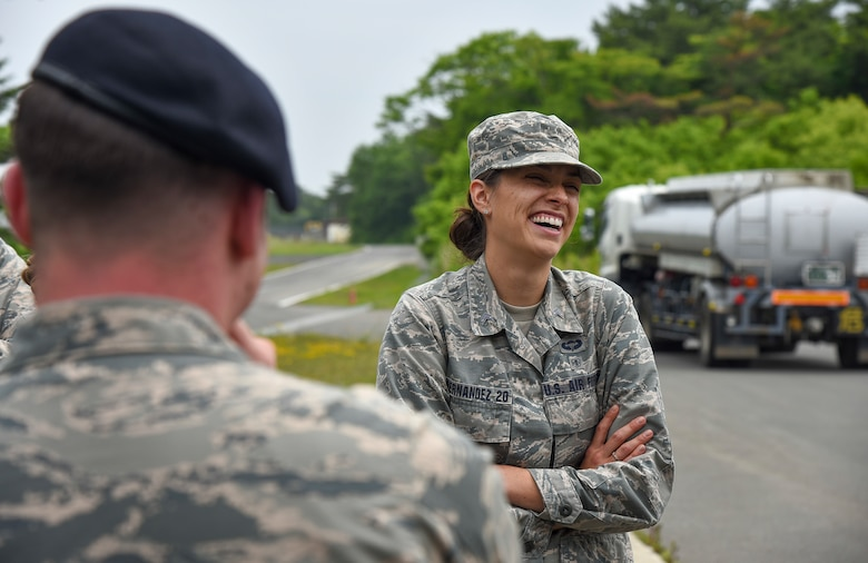 Cadet 2nd Class Jessica Fernandez, a United States Air Force Academy cadet, laughs while having a conversation with Capt. Austin Phillips, the 35th Security Forces Squadron operations officer, during a gate tour at Misawa Air Base, Japan, June 18, 2018. The cadets toured organizations within the 35th Fighter Wing during Operation Air Force, a two-week program that allows cadets to see active duty Air Force life and the different career fields open to them upon graduation. (U.S. Air Force photo by Airman 1st Class Collette Brooks)
