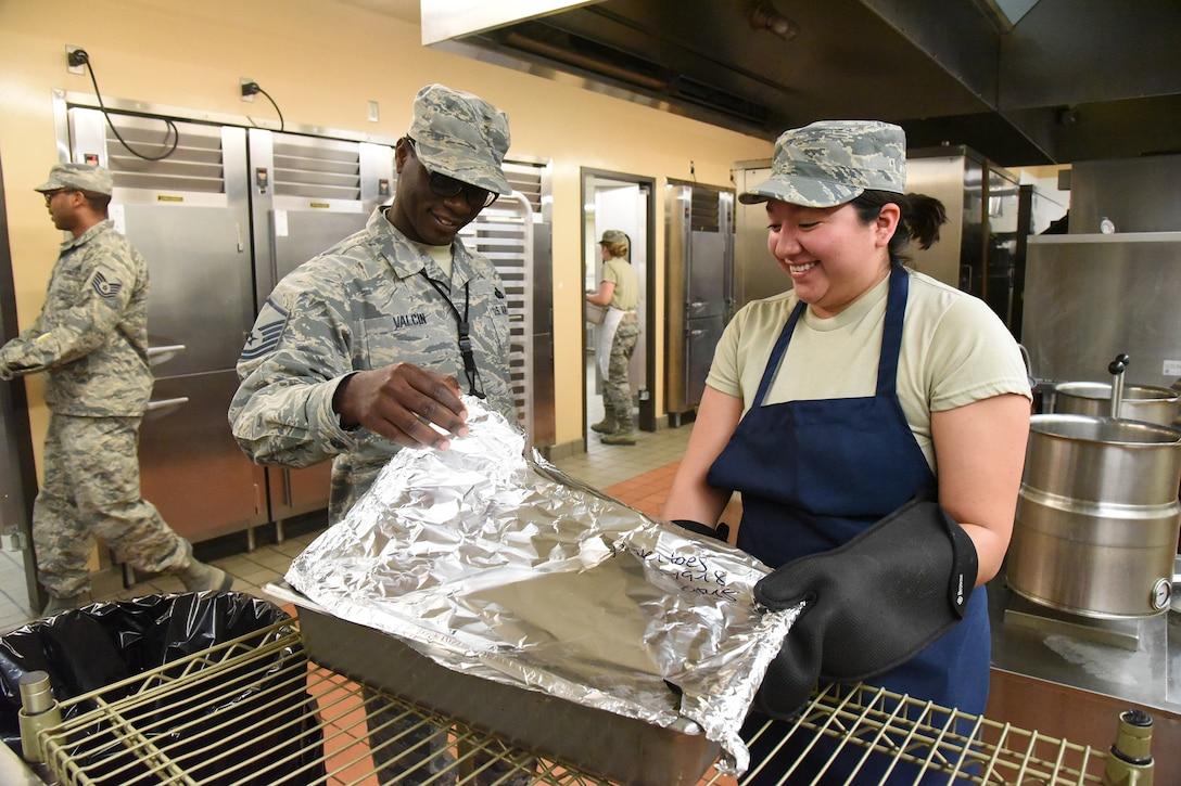 Master Sgt. Wadkey Valcin, of the Air Combat Command (ACC) inspector general team, left, looks over food preparation and questions Airman 1st Class Dominique Martinez, of the 119th Services Flight, during a unit effectiveness inspection (UEI) at the North Dakota Air National Guard Base, Fargo, N.D., May 19, 2018.
