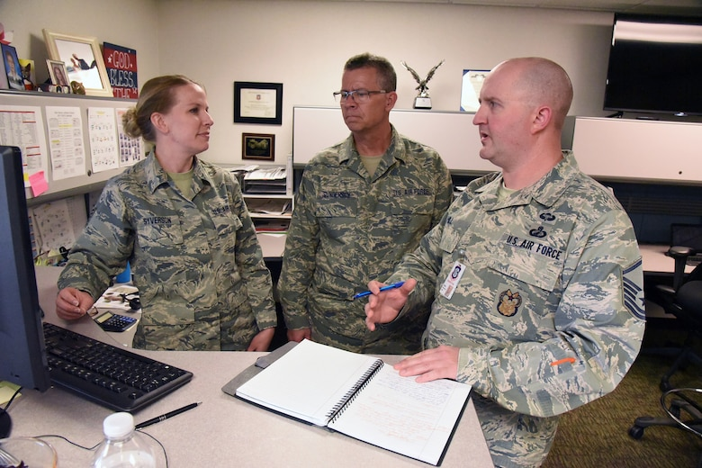 Master Sgt. Brandon Hill, of the Air Combat Command (ACC) inspector general team, right, discusses unit standards and practices with Tech. Sgt. Rachel Syverson, left, and Senior Master Sgt. Lee Gunderson, both assigned to the 119th Logistics Readiness Squadron contracting office, during a unit effectiveness inspection (UEI) at the North Dakota Air National Guard Base, Fargo, N.D., May 19, 2018.