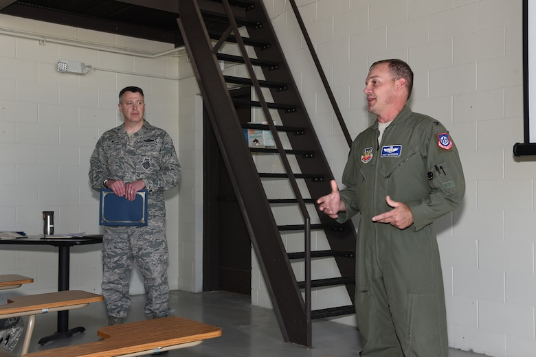 Col. Troy Henderson, the Air Combat Command (ACC) inspector general team chief, right, speaks to a group of 119th Logistics Readiness Squadron personnel as Col. Britt Hatley, the 119th Wing commander looks on during a unit effectiveness inspection (UEI) at the North Dakota Air National Guard Base, Fargo, N.D., May 20, 2018.