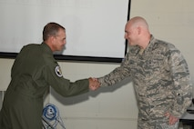 Col. Troy Henderson, the Air Combat Command (ACC) inspector general team chief, left, shakes hands and presents the prestigious inspector general's coin to 2nd Lt. Michael Schuldt, of the 119th Logistics Readiness Squadron, for Schuldt's exceptional performance during a unit effectiveness inspection (UEI) at the North Dakota Air National Guard Base, Fargo, N.D., May 20, 2018.