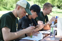 From left to right Senior Airman Joel 'Braxton' Aldridge, Airman 1st Class Abby Swanson and Senior Airman Nathan Reitan, all members of the North Dakota Air National Guard junior enlisted advisory council (JEAC), paint flower pots as part of a service project during a leadership retreat at Fort Ransom State Park, near Fort Ransom, N.D., June 4, 2018.
