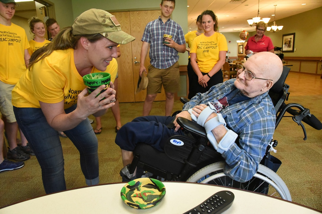 Tech. Sgt. Shelly Fink, of the 119th Wing, presents a potted plant to U.S. Marine veteran Tom Keifer at the Lisbon, N.D. veteran's home June 5, 2018. Fink is among a group of JEAC members visiting the veteran's home as part of a service project following a leadership retreat at Fort Ransom State Park, near Fort Ransom, N.D., June 4, 2018.