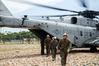 Marines disembark from a military helicopter.