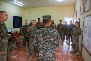 A group of military personnel conduct a briefing.