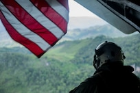 A Marine looks out the back of a helicopter