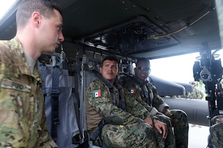Military personnel talk inside a helicopter.