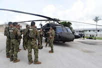 Military personnel talk by a helicopter.