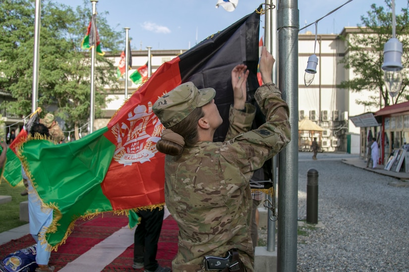 A service member raises the Afghanistan flag.